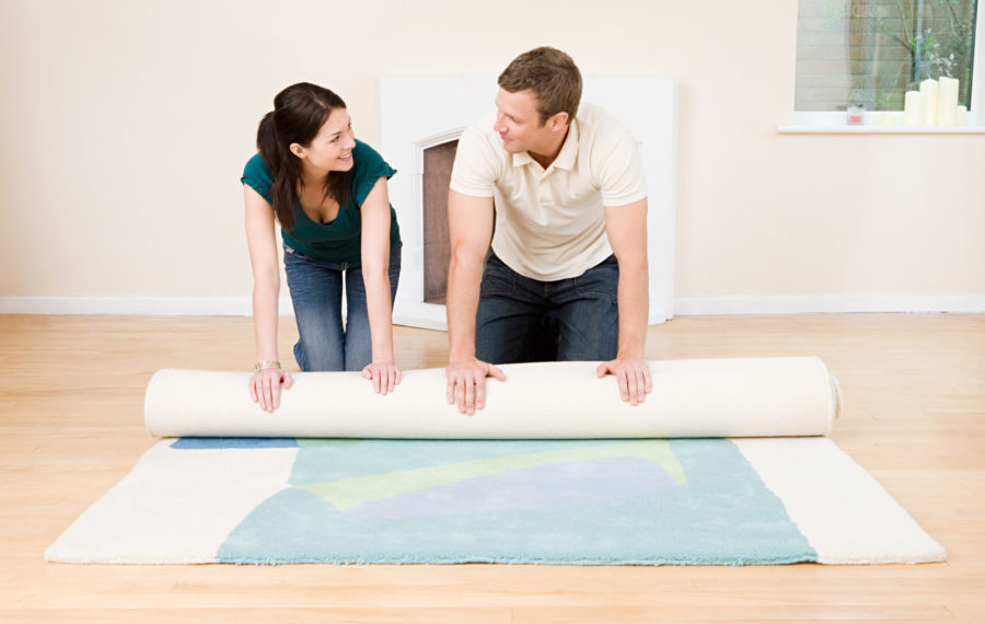 Couple rolling out rug